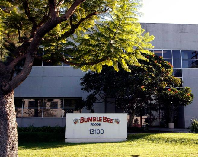 FILE - This Monday, Oct. 15, 2012 file photo shows the Bumble Bee tuna processing plant in Santa Fe Springs, Calif. Bumble Bee Foods has agreed to pay $6 million Wednesday, Aug. 12, 2015, to settle criminal charges in the death of a Los Angeles-area worker who was cooked in an oven with tons of tuna. (AP Photo/Nick Ut, File)